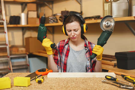 Young brown-hair woman in plaid shirt, gray T-shirt, noise insulated headphones, yellow gloves working in carpentry workshop at wooden table place with different tools, power saw and electric drill Stock Photo