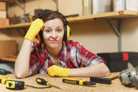 Bewildered perplexed upset young woman in plaid shirt, gray T-shirt, noise insulated headphones, yellow gloves working in carpentry workshop at wooden table place with piece of wood, different tools