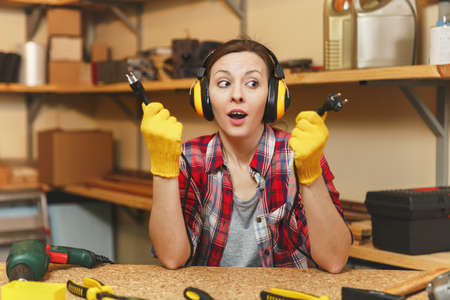 Beautiful crazy fun caucasian young woman in plaid shirt, noise insulated headphones working in carpentry workshop at table place, with two wires from electrical appliances like power drill and saw
