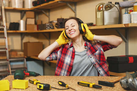 European young woman in plaid shirt, gray T-shirt, noise insulated headphones, yellow gloves listening music, working in carpentry workshop at wooden table place with piece of wood, different tools