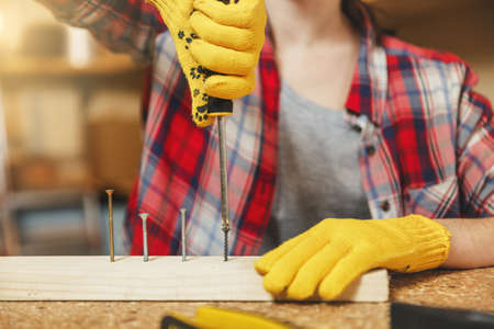 Close up of caucasian young woman in plaid shirt, gray T-shirt, yellow gloves twisting by screwdriver screw, working in carpentry workshop at wooden table place with piece of wood, different tools