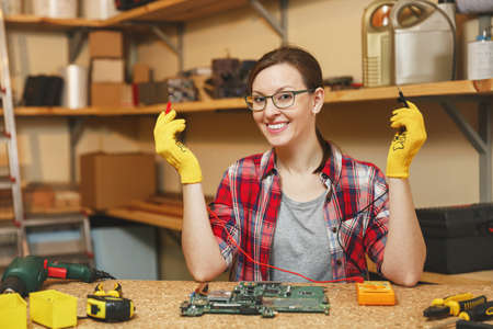 Multimeter for electrician. Pretty young woman in yellow gloves, glasses digital electronic engineer repairing, soldering computer PC motherboard in workshop at wooden table with different tools Stock Photo