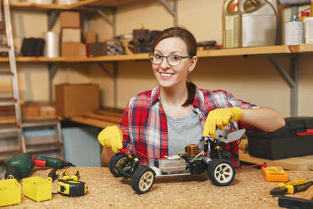 Young woman in plaid shirt, gray T-shirt, yellow gloves making toy car iron model constructor, working in carpentry workshop at wooden table place with different tools. Multimeter for electrician Stock Photo