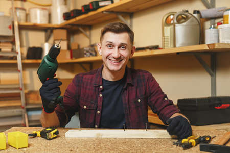 Handsome smiling caucasian young man in plaid shirt, black T-shirt, gloves drilling with power drill in piece of wood, working in carpentry workshop at wooden table place with different tools