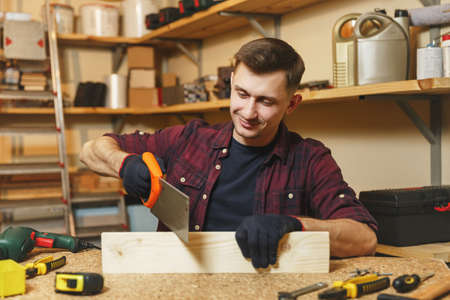 Handsome charismatic smiling caucasian young man in plaid shirt, black T-shirt, gloves sawing wood with saw, working in carpentry workshop at wooden table place with piece of wood, different tools