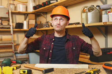 Handsome smiling caucasian young man in plaid shirt, black T-shirt, orange protective helmet, gloves working in carpentry workshop at wooden table place with piece of wood, hammer, different tools