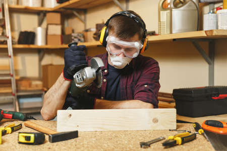Caucasian young man in plaid shirt, black T-shirt, noise insulated headphones, protective mask working in carpentry workshop at wooden table place with different tools, sawing wood with power saw Stock Photo