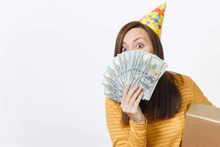 Caucasian pretty fun young happy woman in yellow clothes, birthday party hat holding golden gift boxes with present, hiding behind wad of cash money, celebrating holiday on white background isolated