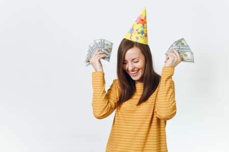 Beautiful caucasian lucky young happy woman in yellow clothes, birthday party hat holding wad of cash money, celebrating holiday on white background isolated for advertisement. Winner with dollars