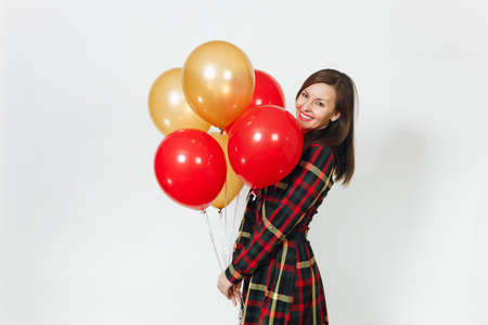 Beautiful caucasian young happy woman in long plaid checkered dress with shy charming smile, red, yellow golden balloons, celebrating birthday, on white background isolated. Holiday, party concept