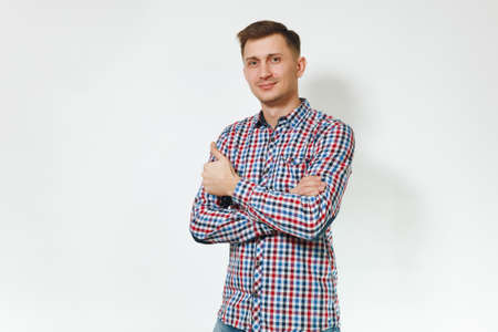 Handsome cheerful positive satisfied caucasian smiling fun young happy man 25-30 years in blue plaid shirt holding hands crossed on white background isolated for advertisement. Emotions concept Stock Photo
