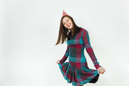 Beautiful caucasian fun young happy woman in plaid dress and birthday party hat with shy charming smile and brown hair, celebrating and enjoying holiday on white background isolated for advertisement Stock Photo
