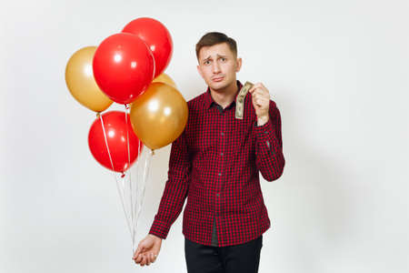 Handsome caucasian sad upset young y man in red plaid shirt with yellow golden balloons, one dollar banknote celebrating birthday, on white background isolated for advertisement. Pure concept