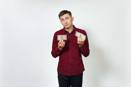 Handsome sad confused annoyed crying caucasian young business man in red shirt holding few banknotes money on white background isolated for advertisement. Concept of poverty and economy