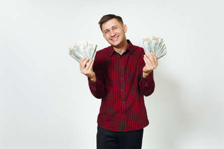 Handsome cheerful positive satisfied caucasian lucky young happy business man 25-30 years in red shirt holding wad of cash money on white background isolated for advertisement. Winner with dollars