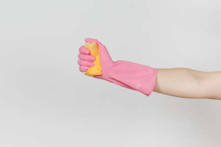 Close up of female hand in pink gloves holds and squeezes yellow-orange sponge for cleaning and washing dishes isolated on white background. Cleaning supplies concept. Copy space for advertisement. Stock Photo