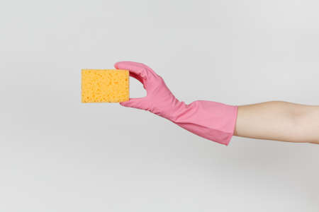 Close up of female hand in pink gloves horizontal holds yellow-orange sponge for cleaning and washing dishes isolated on white background. Cleaning supplies concept. Copy space for advertisement.