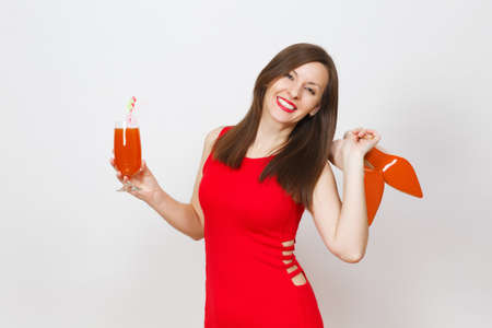 Beautiful glamour fashionable young brown-hair woman in red dress holding glass of drink cocktail, beige shoes with red sole of her shopping isolated on white background. Copy space for advertisement