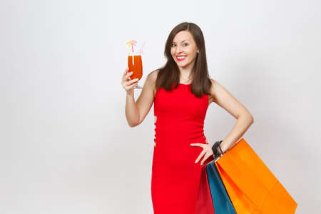 Attractive glamour fashionable young woman in red dress holding glass of drink cocktail, multi colored packets with purchases after shopping isolated on white background. Copy space for advertisement