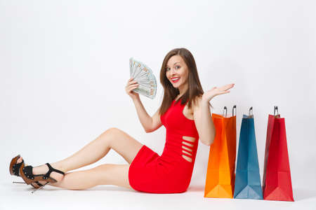 Beautiful glamour fashionable young woman in red dress sitting with cash dollars, multi colored packets with purchases after shopping isolated on white background. Copy space for advertisement
