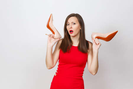 Attractive glamour caucasian fashionable young pensive perplexed brown-hair woman in red dress getting beige shoes with red sole of shopping isolated on white background. Copy space for advertisement Stock Photo