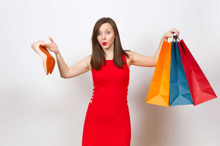 Attractive impressive glamour caucasian fashionable young brown-hair woman in red dress holding beige shoes with red sole, multi colored packets with purchases, shopping isolated on white background