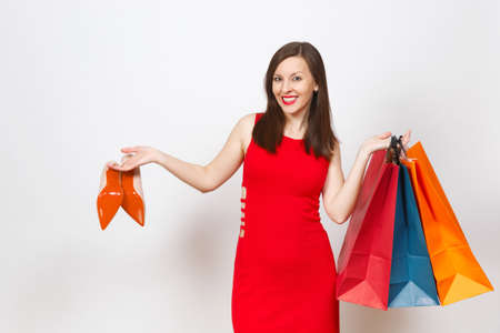 Attractive impressive glamour caucasian fashionable young brown-hair woman in red dress holding beige shoes with red sole, multi colored packets with purchases, shopping isolated on white background 版權商用圖片 - 101560693