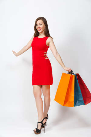 Full length of attractive glamour caucasian young brown-hair woman in red dress holding multi colored packets with purchases after shopping isolated on white background. Copy space for advertisement
