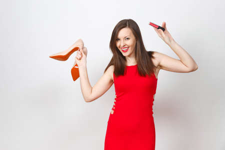 Beautiful glamour caucasian fashionable young brown-hair woman in red dress holding beige shoes with red sole, lipstick of her shopping isolated on white background. Copy space for advertisement Фото со стока