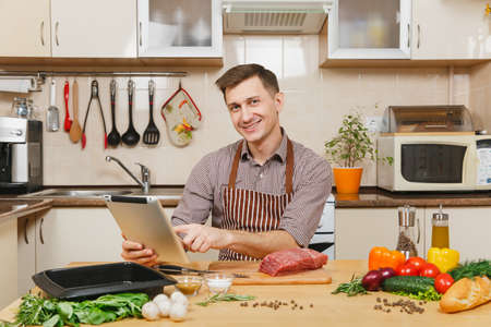 Young man in apron sitting at table with vegetables, looking for recipe in tablet, cooking at home preparing meat stake from beef, in light kitchen with wooden surface, full of fancy kitchenware Stock Photo