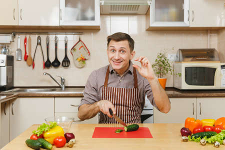 Handsome smiling caucasian young man in an apron, brown shirt sitting at table, showing fingers small distance, cuts vegetable for salad with knife in light kitchen. Dieting concept. Cooking at home Standard-Bild