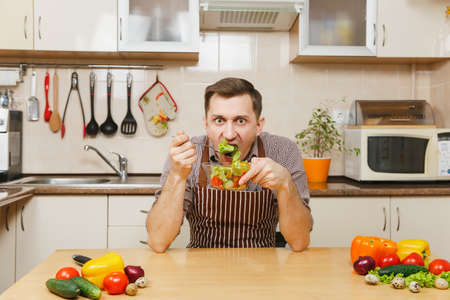 Attractive hungry caucasian young man in apron, brown shirt sitting at table with vegetable salad in bowl, eating in light kitchen. Dieting concept. Healthy lifestyle. Cooking at home. Prepare food