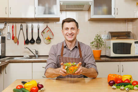 Handsome smiling European young man in apron, brown shirt sitting at table with vegetable salad in bowl in light modern kitchen. Dieting concept. Healthy lifestyle. Cooking at home. Prepare food