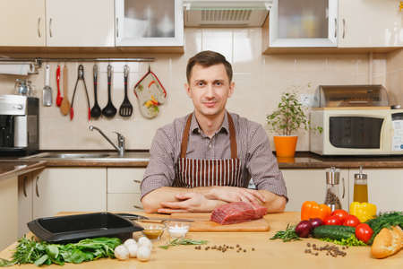 Handsome caucasian young man in apron sitting at table with vegetables, cooking at home preparing meat stake from pork, beef or lamb, in light kitchen with wooden surface, full of fancy kitchenware
