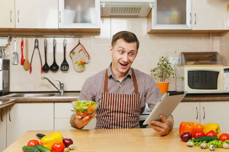 Handsome smiling caucasian young man in apron, brown shirt sitting at table with vegetable salad in bowl and tablet in light kitchen. Dieting concept. Healthy lifestyle. Cooking at home. Prepare food