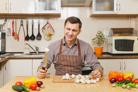 Handsome caucasian young man in apron, brown shirt sitting at table with vegetable, cutting champignon mushrooms in light kitchen. Dieting concept. Healthy lifestyle. Cooking at home. Prepare food