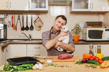 Young man in apron sitting with furry cat at table with vegetables, cooking at home preparing meat whitestake from pork, beef or lamb, in light kitchen with wooden surface, full of fancy kitchenware