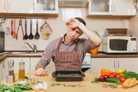 Tired stress upset young man in apron sitting at table with vegetables, cooking at home preparing meat stake from pork, beef or lamb, in light kitchen with wooden surface, full of fancy kitchenware