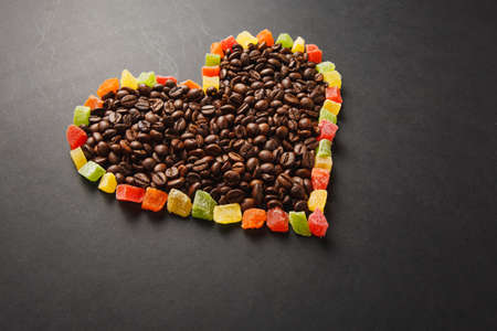 Colorful candied fruits in the form of heart with brown coffee beans isolated on black background for design. Saint Valentine's Day card on fabruary 14, holiday concept. Copy space for advertisement