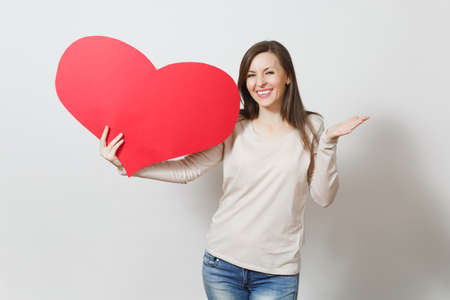 Pretty fun young smiling woman holding big red heart in hands isolated on white background. Copy space for advertisement. With place for text. St. Valentines Day or International Womens Day concept