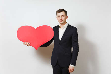Young handsome man in suit holding big red heart isolated on white background. Copy space, advertisement. Place for text. St. Valentines Day, International Womens Day, birthday, holiday concept