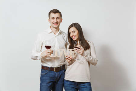 Young caucasian couple. Happy smiling man and woman in love in casual light clothes, jeans making toast, drinking from glasses of red wine isolated on white background. Copy space for advertisement