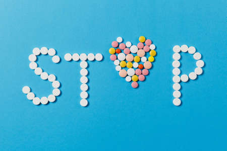 Medication white, colorful round tablets in word Stop isolated on blue background. Pills heart shape, form, letter. Concept of health, treatment, choice, healthy lifestyle. Copy space advertisement Stok Fotoğraf