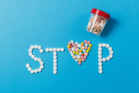 Medication white, colorful round tablets in word Stop isolated on blue background. Pills heart shape form, analysis jar letter. Concept of health treatment choice healthy lifestyle. For advertisement Stock Photo