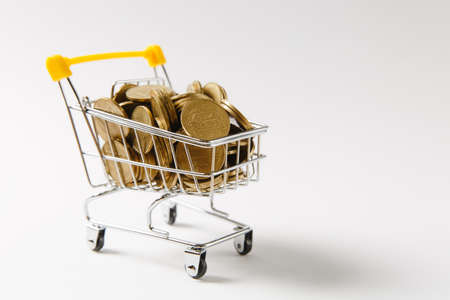 Close up of supermarket grocery push cart for shopping with yellow plastic elements on handle filled with golden coins isolated on white background. Concept of shopping. Copy space for advertisement. Reklamní fotografie
