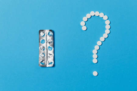Medication white round tablets arranged in question mark shape isolated on blue color background. Packing of pills, sign. Concept of health, treatment, choice, healthy lifestyle Stock Photo