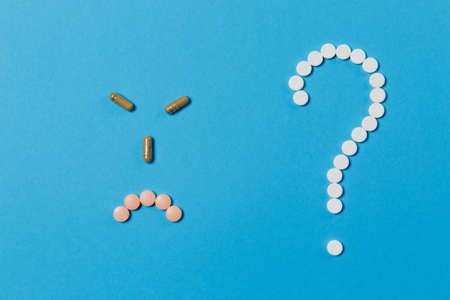 Medication white round tablets arranged in question mark shape isolated on blue color background. Smile sad neutral face from pills, sign. Concept of health, treatment, choice, healthy lifestyle