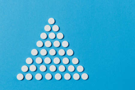 Medication white round tablets arranged in form of triangle isolated on blue color background. Pills geometric pyramid shape. Concept of health, treatment, choice, lifestyle. Copy space advertisement