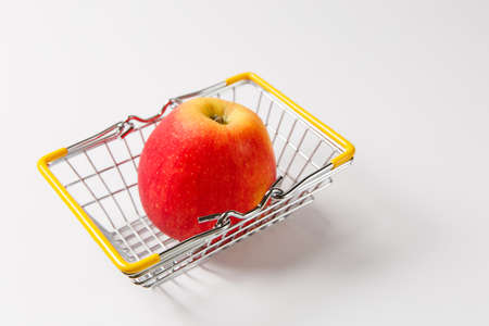 Close up of metal grocery basket for shopping in supermarket with lowered yellow handles with bright red apple isolated on white background. Concept of shopping. Copy space for advertisement.