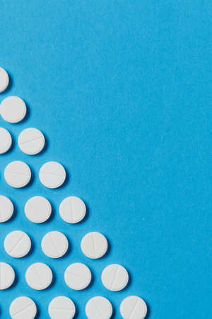 Medication white round tablets arranged in form of triangle isolated on blue color background. Pills geometric pyramid cropped shape. Concept of health treatment choice, healthy lifestyle. Copy space Stock Photo